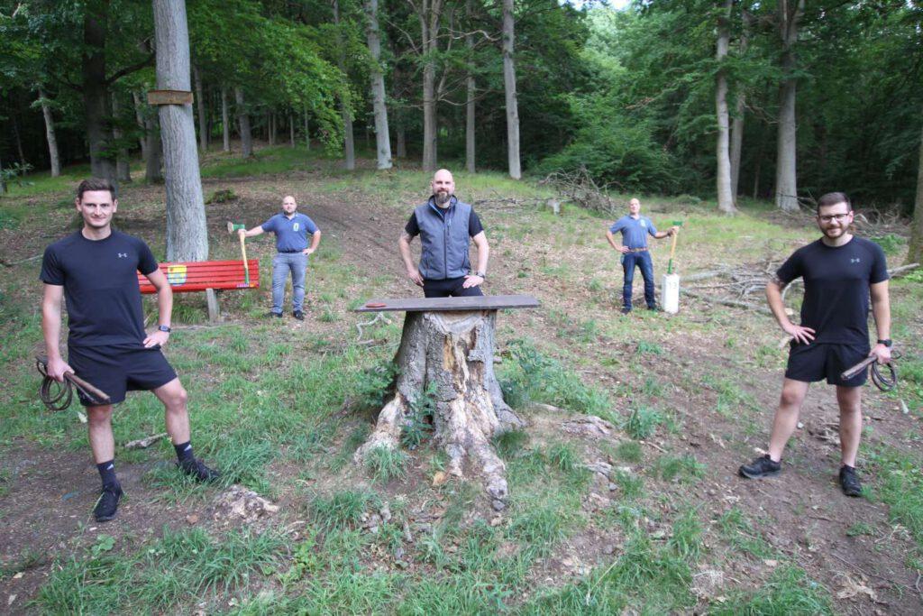 5 Männer im Wald. Mit Äxten und Peitschen trainieren sie.