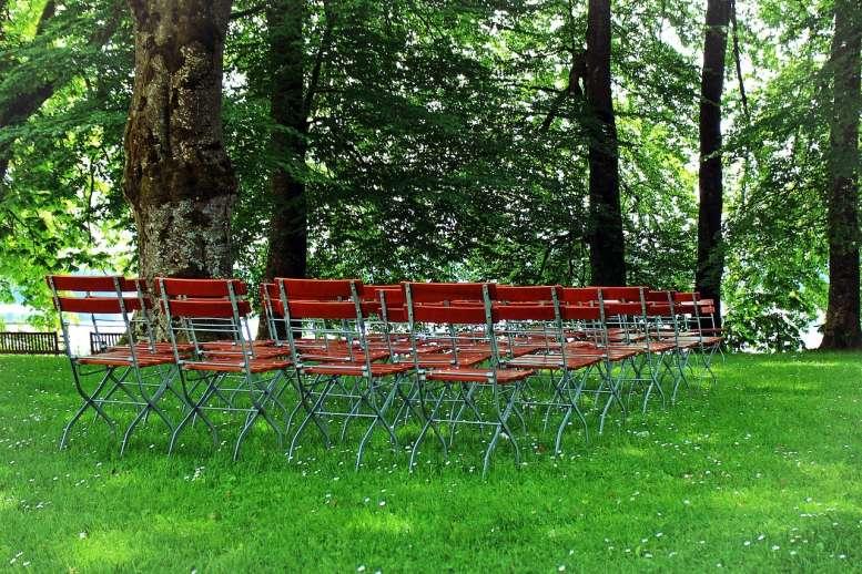 Stühle auf einer Wiese unter Bäumen
