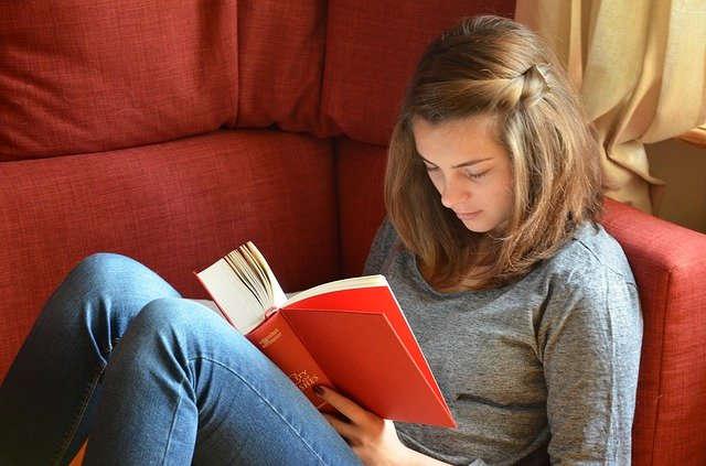Lesendes Mädchen auf einer Couch.