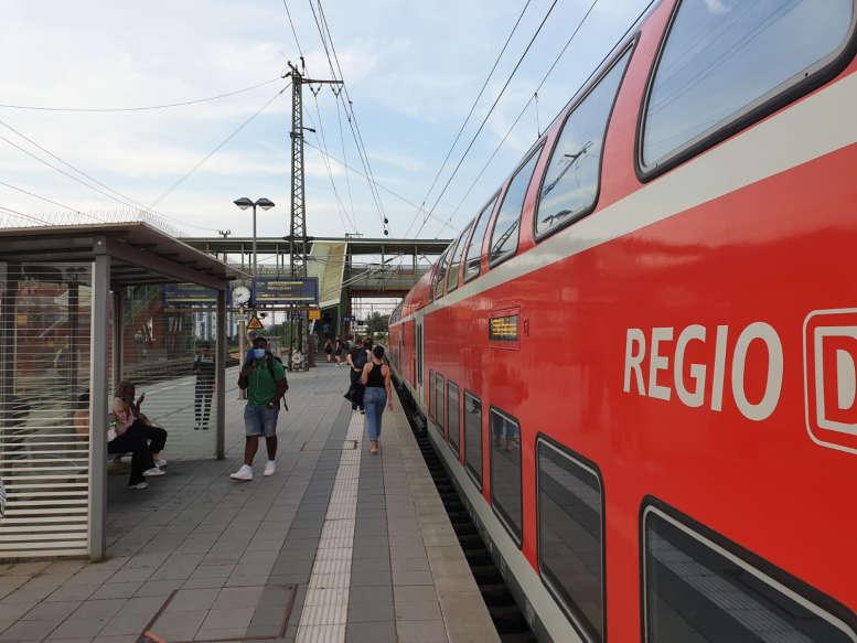 Am Bahnhof steigen Leute in die Regionalbahn ein
