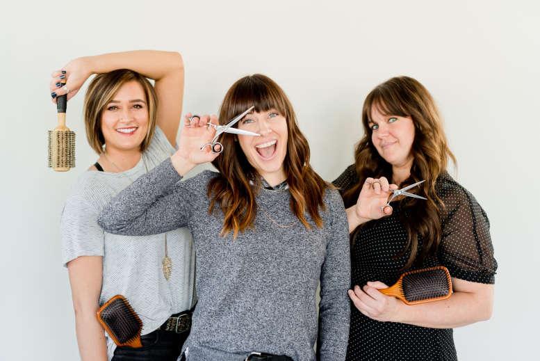 3 junge Frisörinnen mit Bürsten und Scheren.