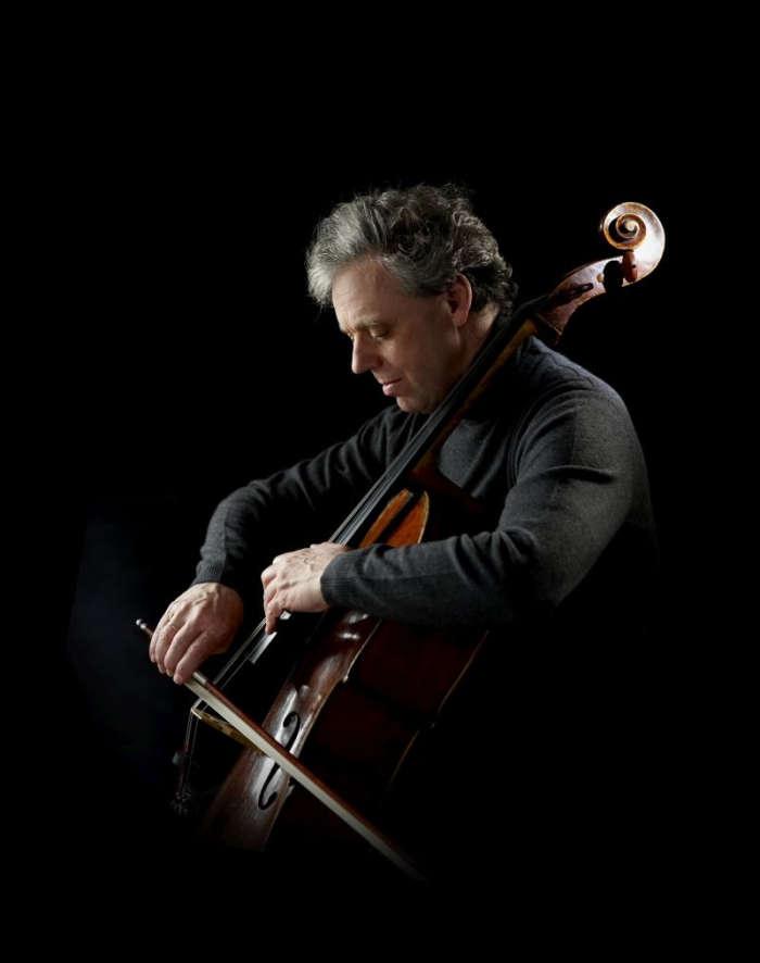 Cellist an seinem Instrument vor schwarzem Hintergrund