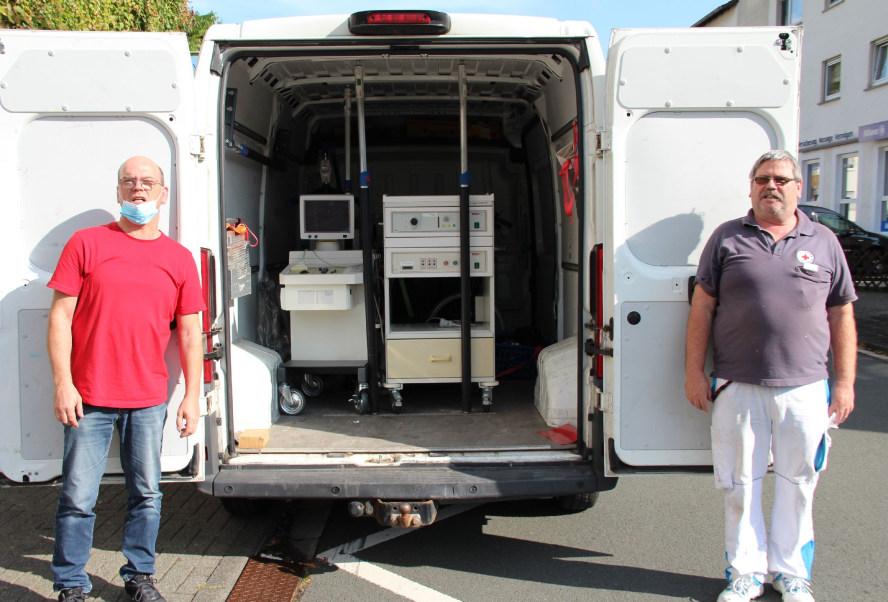 2 Männer vor geöffnetem Transporter mit Hilfsgütern