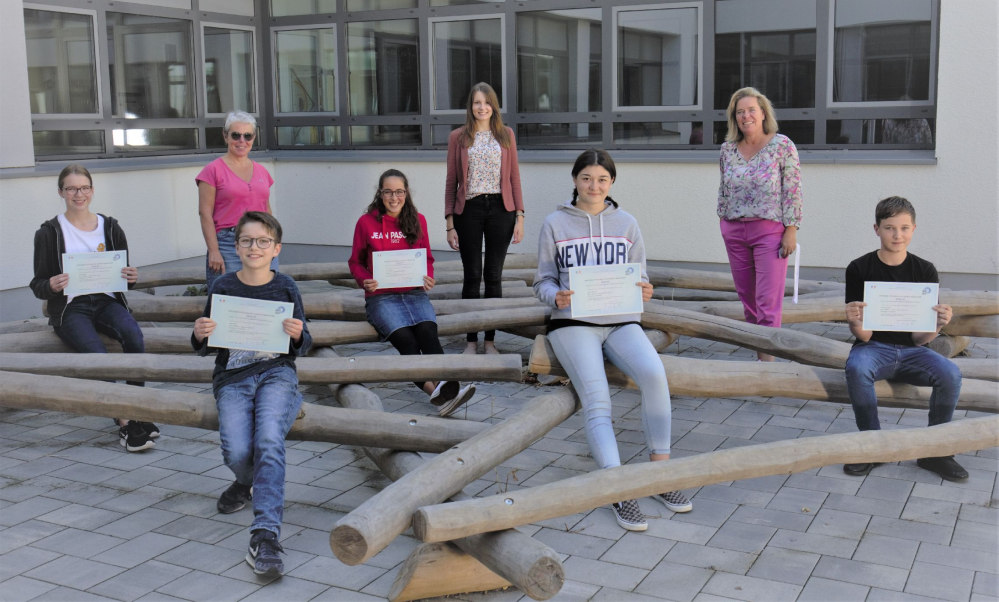 Schüler und Lehrer sitzend mit ihren Zertifikaten.