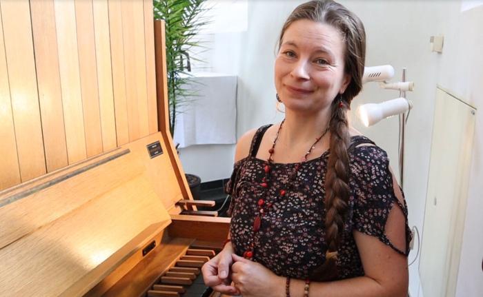 Frau im Sommerkleid an einer Orgel