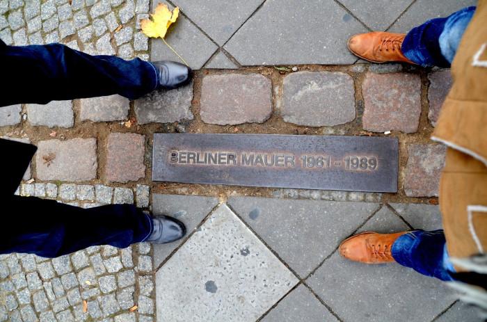 2 Menschen stehen an der Stelle an der früher die Berliner Mauer stand. Eine Gedenktafel ist im Boden eingelassen.
