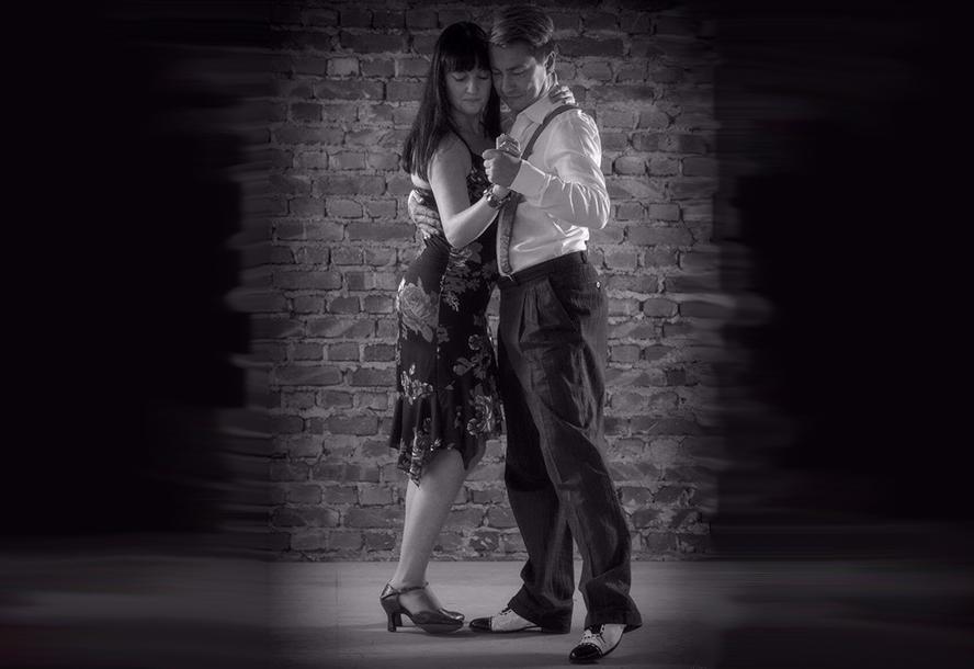 Attraktives Tanzpaar vor Backstein-Hintergrund