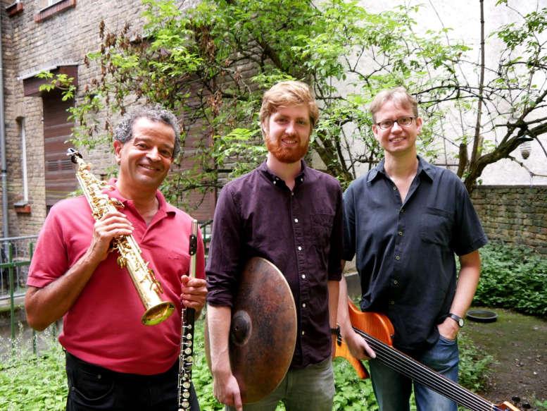 3 Musiker im Garten. Mit Instrumenten.