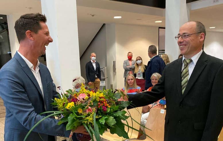 2 Männer lachen miteinander. Einer reicht einen Blumenstrauß