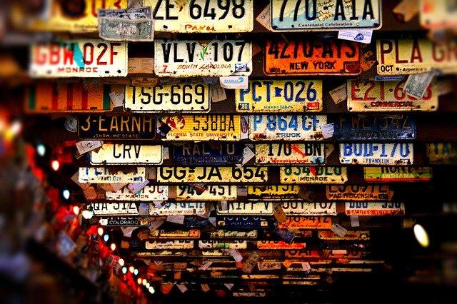 verschiedene ausländische Nummernschilder/Kennzeichen hängen an der Decke