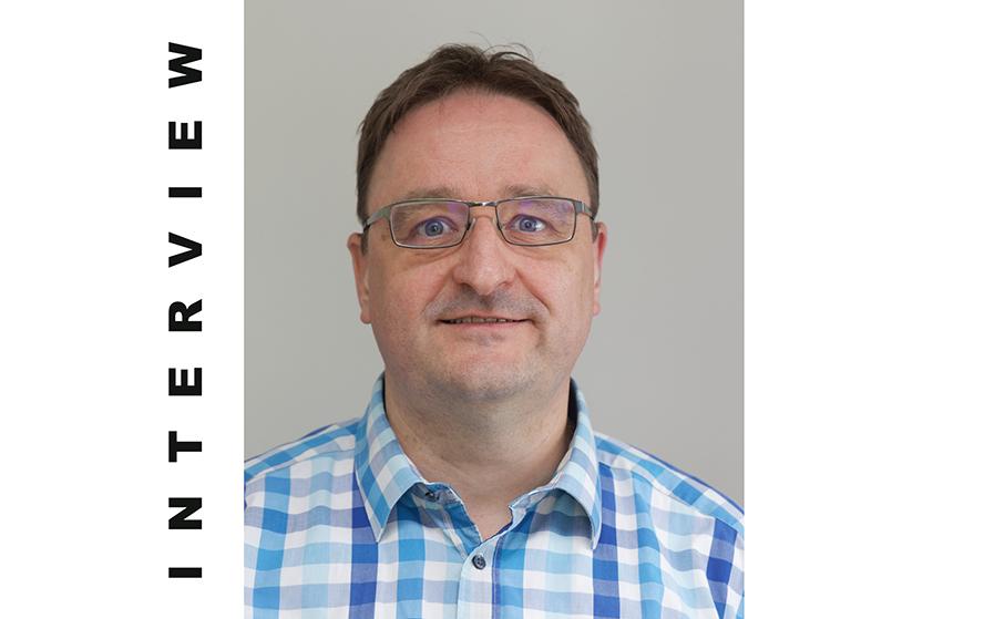 Mann, Mitte 40, mit Brille und kariertem Hemd. Porträtfoto