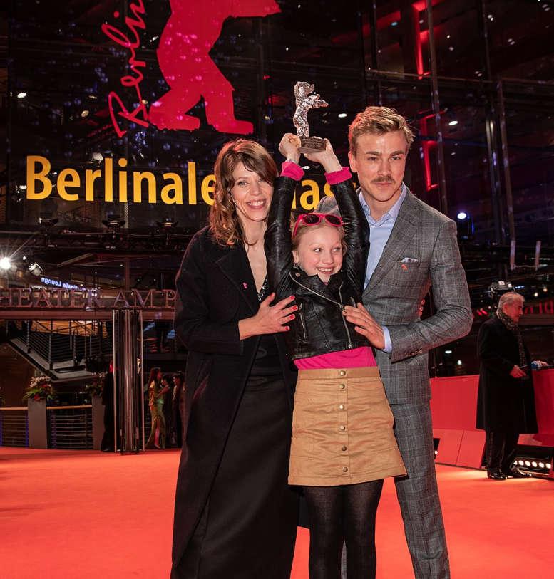 Mann, Frau, Mädchen vor dem berlinale-Logo auf einer Bühne mit dem Silbernen Bären