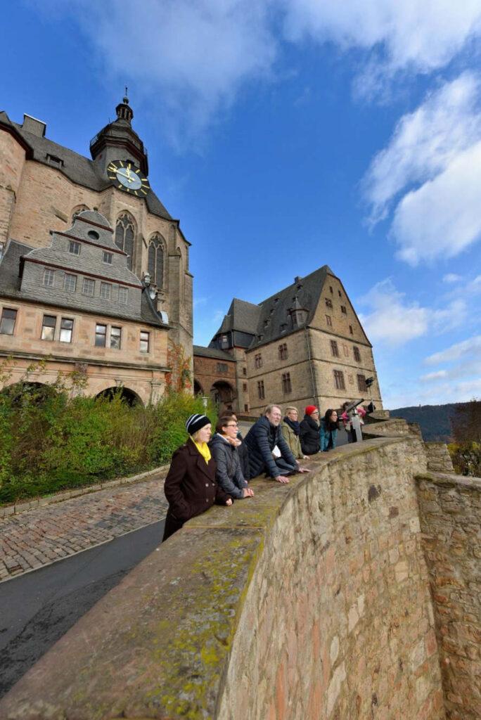 Marburger Schloss und 8 Leute davor an der Mauer.