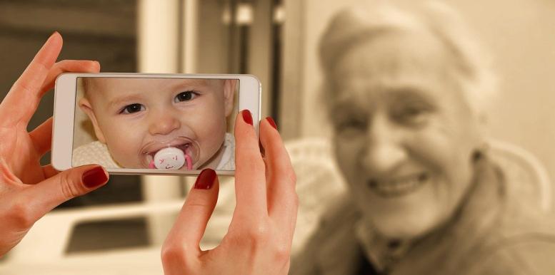 Alte Frau und ein Baby auf dem Handy-Display