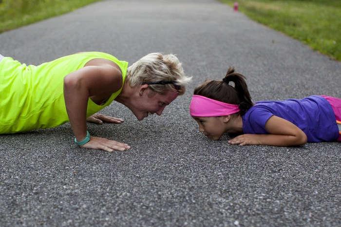 Blonde Frau und farbiges Mädchen machen Liegestützen auf der Asphaltstraße