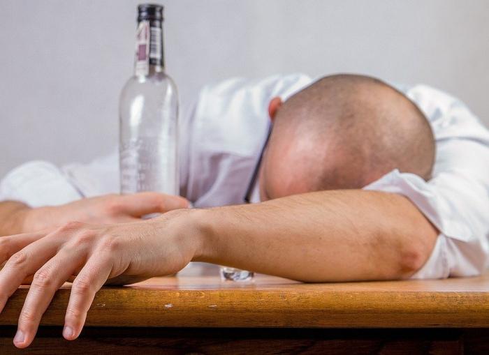 Betrunkener Mann mit leerer Wodkaflasche liegt über den Tisch gebeugt