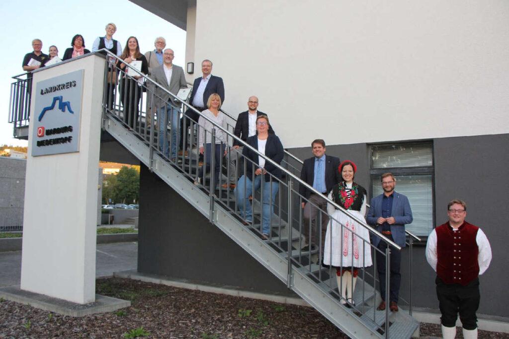 AUf einer Treppe sind etwa 20 Leute mit Abstand platziert.