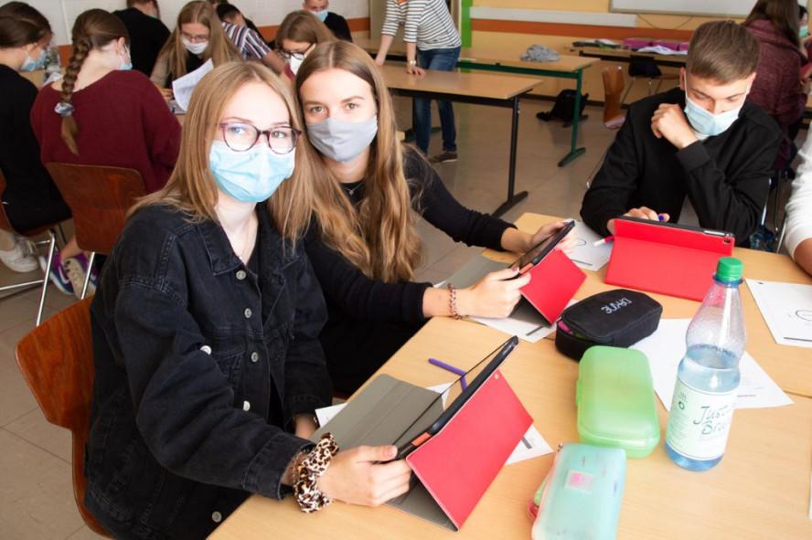 Schülerinnen und Schüler am Arbeitgsplatz /Schreibtisch. Mit Masken