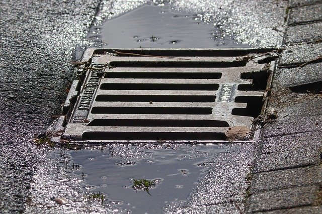 Gullydeckel auf regennasser Straße. Verschließt den Schacht