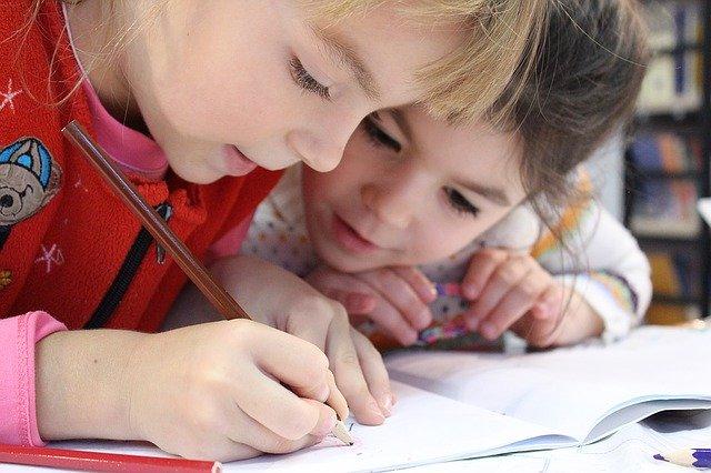 2 Kinder schreiben und stecken die Köpfe zusammen