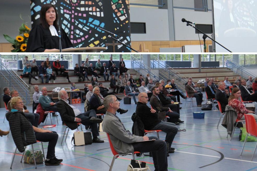 Zuschauer und Pfarrerin mit viel Platz drumherum