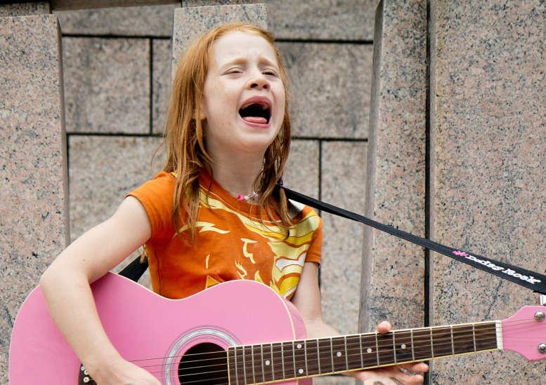Mädchen mit Gitarre singt mit Inbrunst