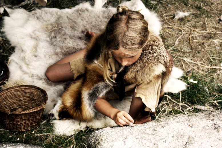 In Felle gekleidetes Mädchen ritzt etwas in einen Felsen