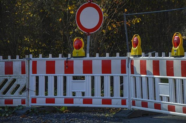 Straßensperrung mit Absperrgitter und Schild