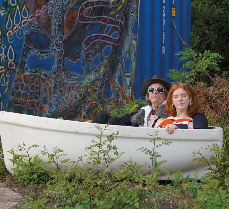 Mann und Frau (2 Darsteller) in einem Boot vor blaugemustertem Vorhang