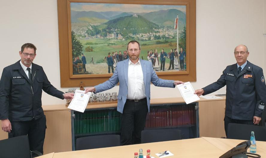 3 Männer die sich die Hände entgegenreichen und jeweils eine Urkunde miteinander halten.