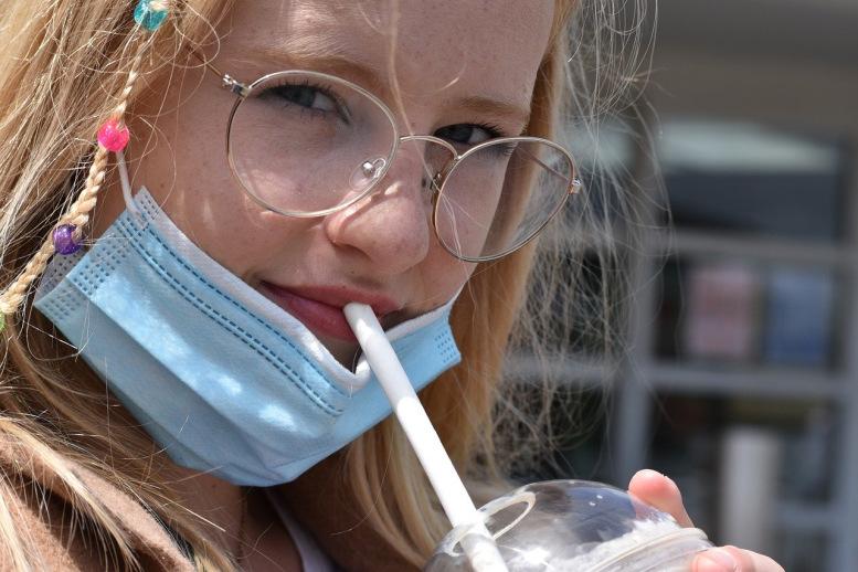 Kind mit Maske trinkt ein Getränk mit Halm