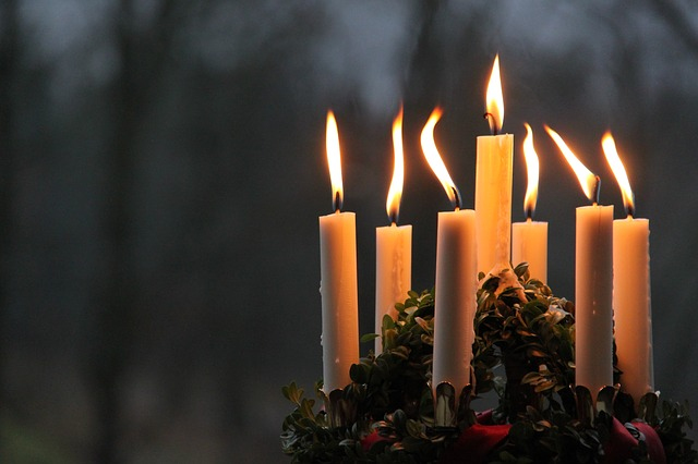 7 brennende Kerzen im Dunkeln