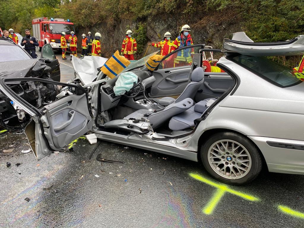 Aufgeschnittener BMW und dahinter Einsatzkräfte der Feuerwehr