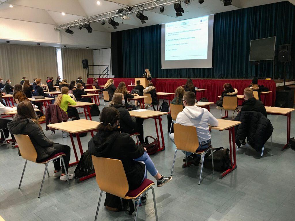 Schüler an Pulten - vorn eine Fachkraft die Vortrag hält