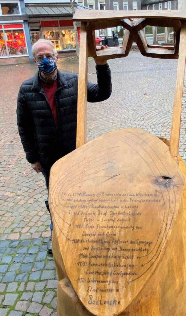 Ein Mann steht am geschnitzten Pult .
