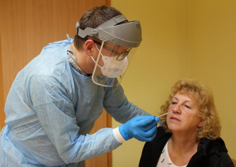 Vermummter Mediziner testet alte Frau