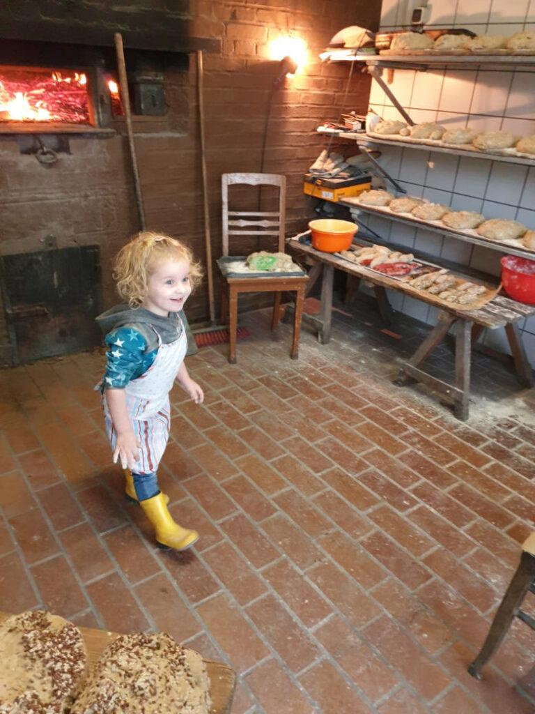 Kleines Mädchen mit Schürze im Backhaus. Feuer im Ofen.