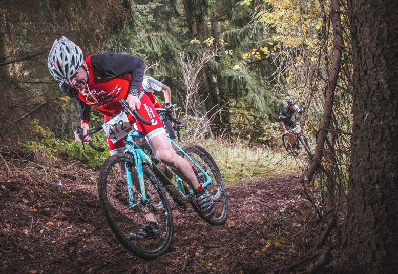Mann mit Fahrrad im Wald