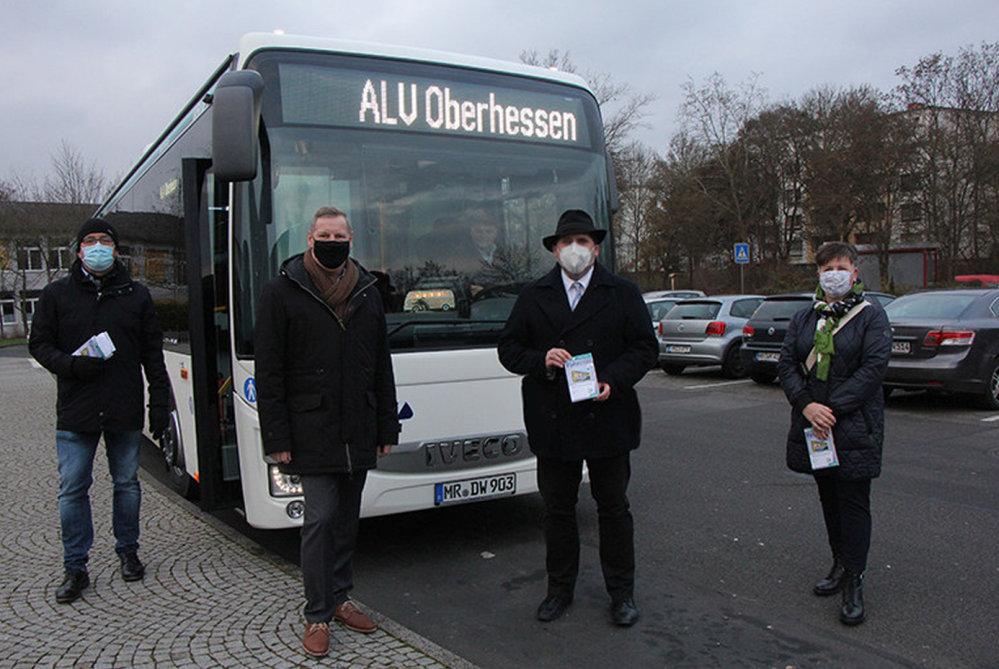 4 Maskierte vor einem Linienbus