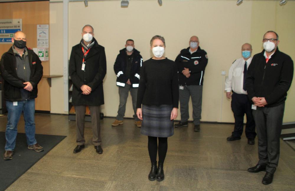 7 Leute mit Masken stellen sich zum Gruppenfoto. Darunter als einzige Frau die Landrätin