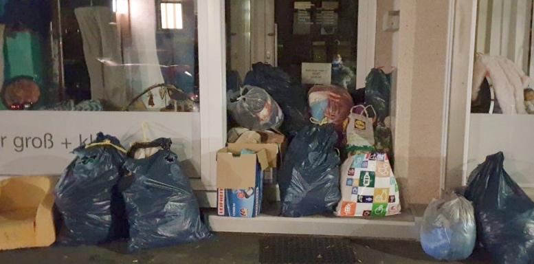 vor einem Eingang liegen haufenweise gefüllte Tüten und Säcke.
