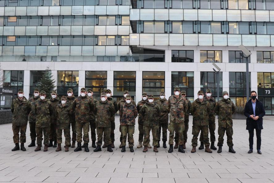20 Soldatinnen und Soldaten mit Landrat vor hohem Gebäude