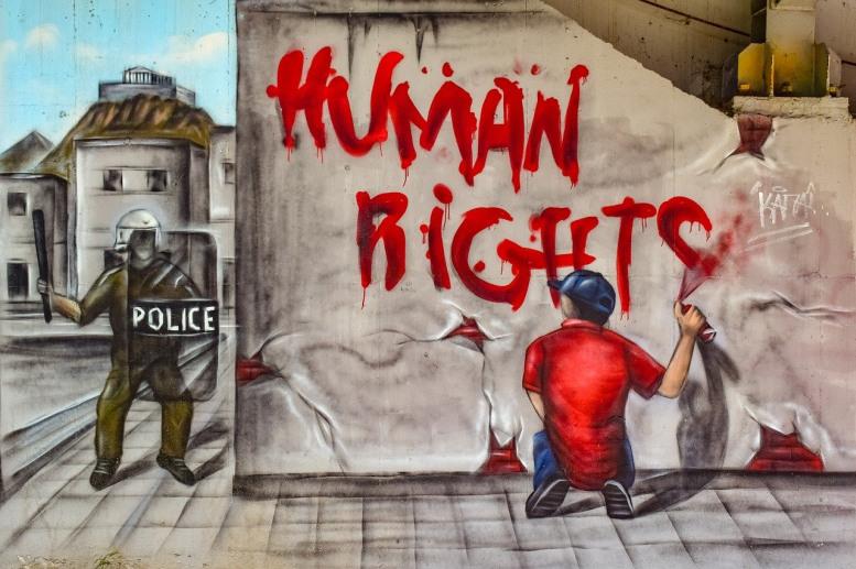 """Mann sprüht """"Human Rights"""" an eine Hauswand"""