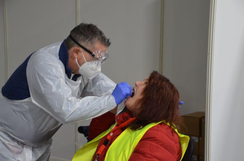 Arzt nimmt Patientin einen Rachenabstrich