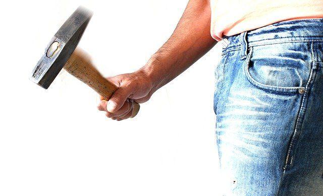Mann in Jeans und Shirt mit einem Hammer in der Rechten