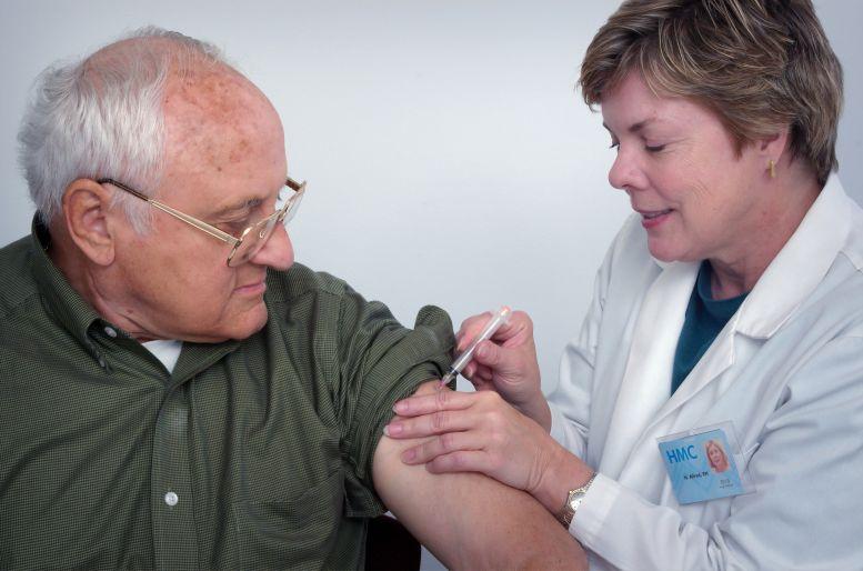 Senior wird von Frau im weißen Kittel geimpft.