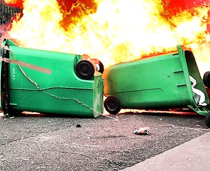 auf der Straße liegende, brennende grüne Mülltonnen.