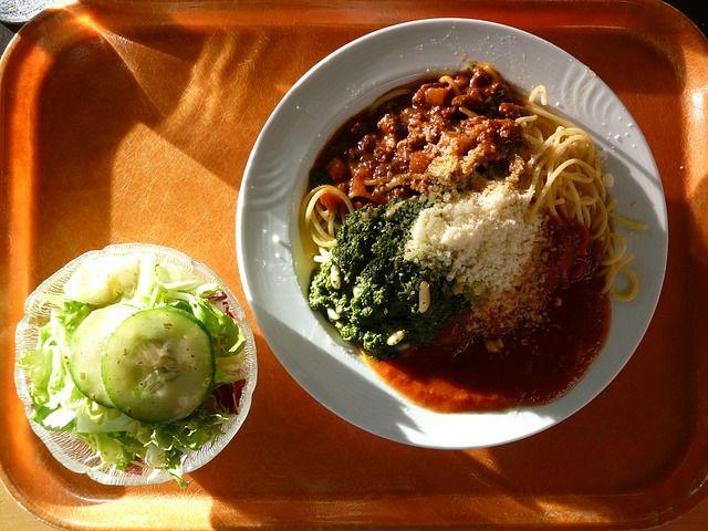 EIn Tablett mit Spaghetti mit Soße und ein Schälchen Salat