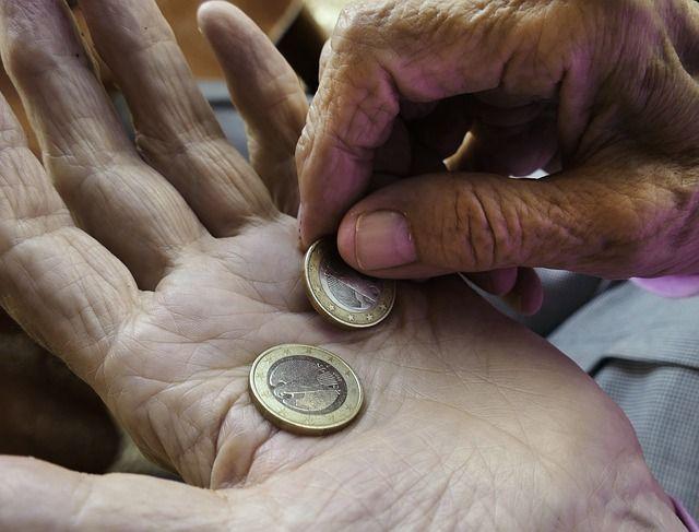 2 Hände einer alten Person die 2 Euro zählen.