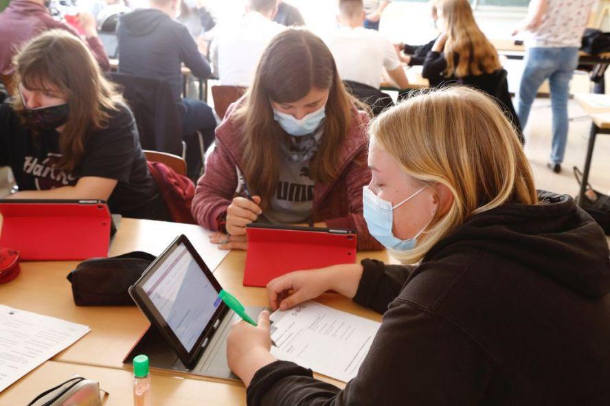 Schülerinnen mit Masken sitzen am iPad und arbeiten.